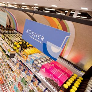 Grocery store shelves stocked with food with Kosher sign hanging above