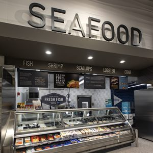 Grocery store seafood counter with sign that says seafood and fresh fish case