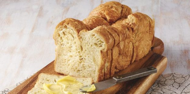 Croissant loaf with slice topped with butter on dark wood board on light wood background
