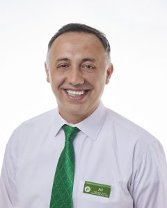 Man in white dress shirt and green tie smiling in front of white background