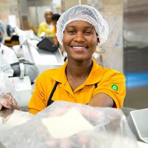 Woman in orange Publix deli uniform wearing hairnet smiling while working