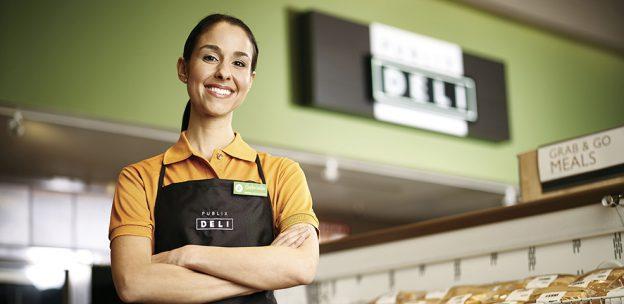 Woman in Publix deli clerk uniform standing in front of Publix deli sign smiling