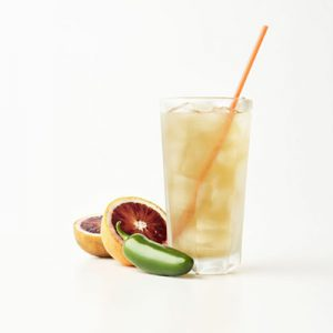 Tea in a glass with a straw next to a blood orange and pepper on a white background