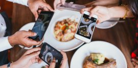 People Holding Phones Taking Photos of Food