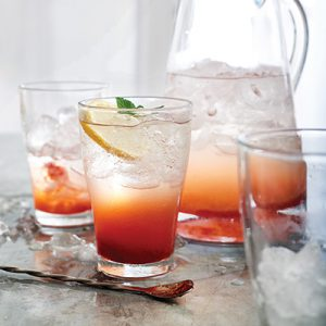 Strawberry Lemon Spritzers in two cups and a pitcher with empty cup off to the side. Drink in front topped off with lemon slice.