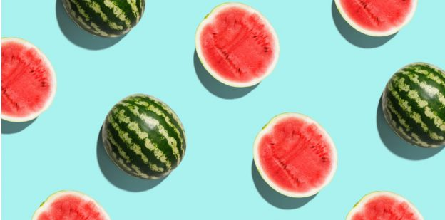 Whole and half watermelons on a bright blue background