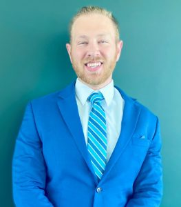 Man in blue suit jacket and white dress shirt and blue striped tie smiling in front of light blue background.
