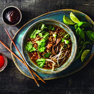 Pho noodle soup in large bowl on tray next to limes, chopsticks and brown sauce in small bowl.