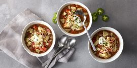 Three bowls of chicken tortilla soup on light grey background next to spoons and jalapenos.