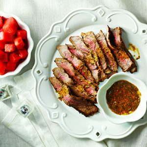 Steak on white plate with chili ginger sauce and watermelon in a small bowl on a white background