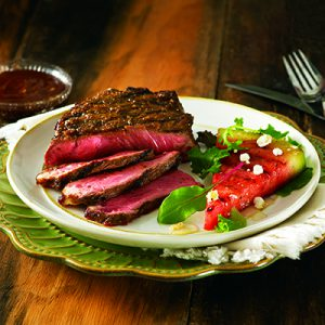 Steak and watermelon on white plate on wood background