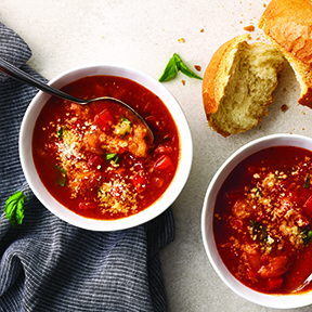 Tomato soup in two white bowls next to bread and grey cloth on white background.