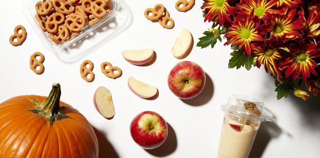 A pumpkin, a parfait, 2 whole apples and apple slices, flowers and pumpkin spice pretzels laying on white background