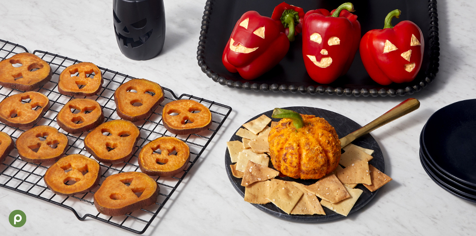 Sweet potatoes, cheese ball with crackers and bell peppers on a white background.