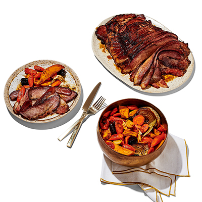 Sliced brisket on a serving platter, mixed vegetables in a bowl on a white napkin, a white plate with brisket and vegetables accompanied by a fork and knife.