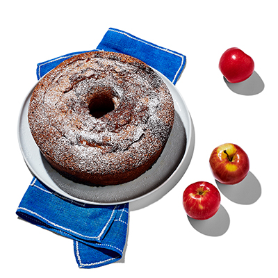 Apple cake served on a white plate with a blue serving napkin, with three red apples off to the right side.