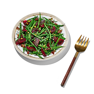 Green bean and beat salad on a white plate with a serving fork off to the side.