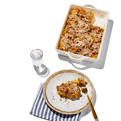 Kugel in a rectangular serving platter, a round plate with a serving of kugel and a fork on a blue and white napkin with a glass of water.