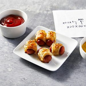 Pigs in a blanket on a white plate with ketchup in a white bowl and napkin with football plays behind plate.
