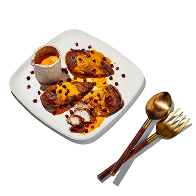 Chicken served with an orange sauce with pomegranate seeds on top, served on a square white plate with a fork and spoon on the side.