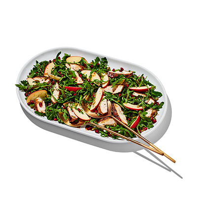 Greens with sliced apple and pomegranate seeds on a white platter with gold serving utensils.