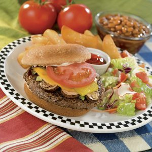 Burger with cheese and tomato. Top bun off to the side. Salad and fries on the plate. Bowl of beans and fresh tomatoes in the background.