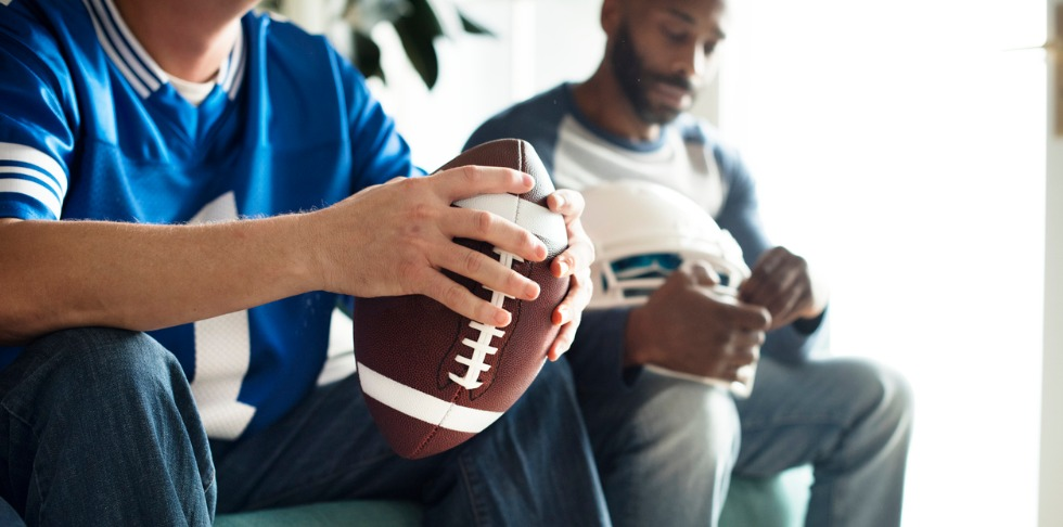 Person sitting down holding a football in a blue jersey with another person in the background holding a white helmet.
