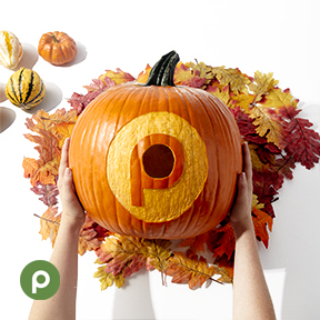 Hands holding pumpkin with carved Publix logo over leave next to small pumpkins