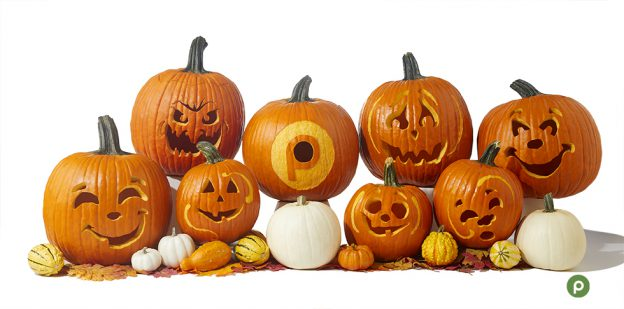 Stacked carved pumpkins on white background