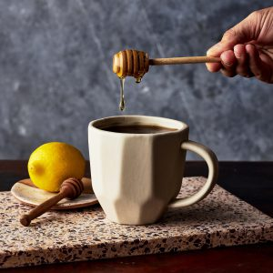 white tea mug with tea and honey dripping into cup