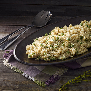 Long plate of risotto on dark table with checkered napkin
