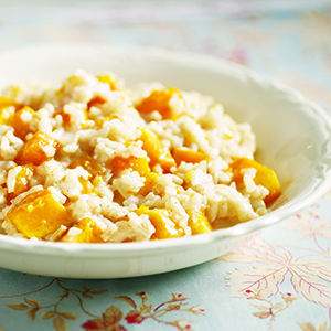 Bowl of pumpkin risotto in white bowl on floral table