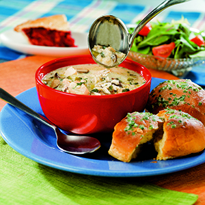 Risotto soup in red bowl next to chive biscuits on green napkin