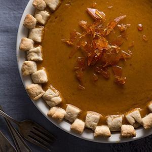 Pumpkin pie topped with sugar shards on dark grey surface