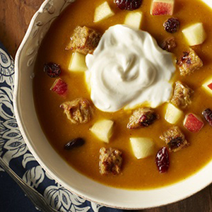 Pumpkin soup in a white bowl on a navy blue cloth and wood surface