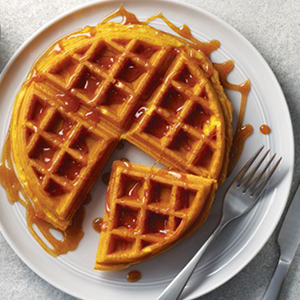 Pumpkin waffle on white plate drizzled with syrup
