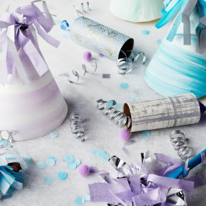 Homemade party hats and party poppers and confetti on grey background
