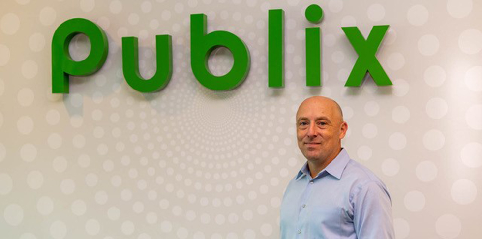 Man in blue dress shirt standing in front of Publix logo on wall