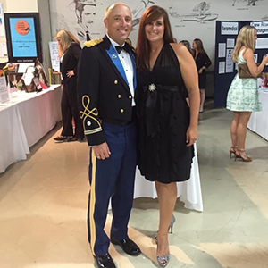 Man in military outfit standing next to woman in dress at military ball.