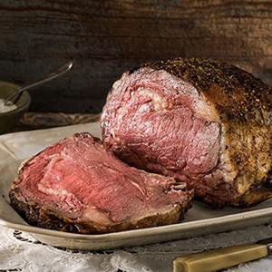 Sliced rib roast on large plate on dinner table.