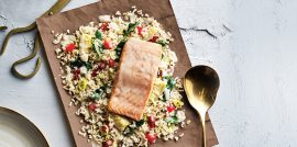 Dijon cream salmon on bed of quinoa on brown parchment next to gold spoon and scissors on light surface.