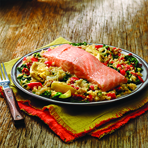 Dijon cream salmon on bed of quinoa on plate and colored cloth napkins on wood surface.