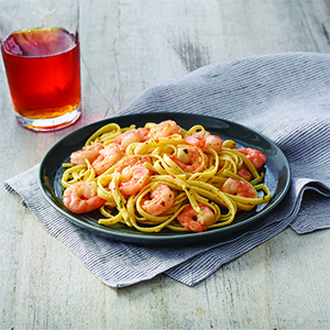 Shrimp and pasta on grey plate and light grey napkin next to cup of tea on light grey surface.