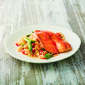 Sweet chili fish on bed of rice and vegetables on light grey wood surface.