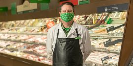 Meat Cutter associate standing in front of meat department in Publix store.