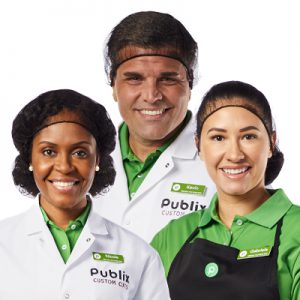 3 meat cutter associates wearing hairnets and Publix uniforms smiling in front of white background.