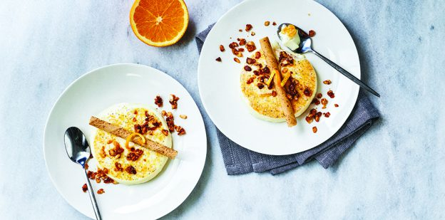 Orange-vanilla panna cotta on white plates on marble surface.