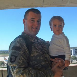 Man in military uniform holding young child.