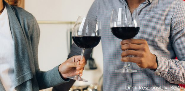 Couple standing in kitchen toasting glasses of red wine.