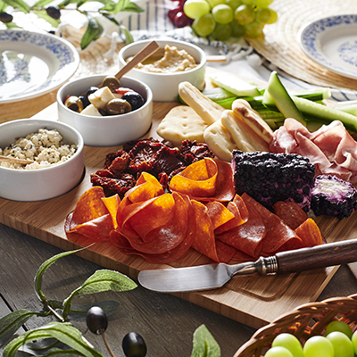 Charcuterie board including meats and veggies.